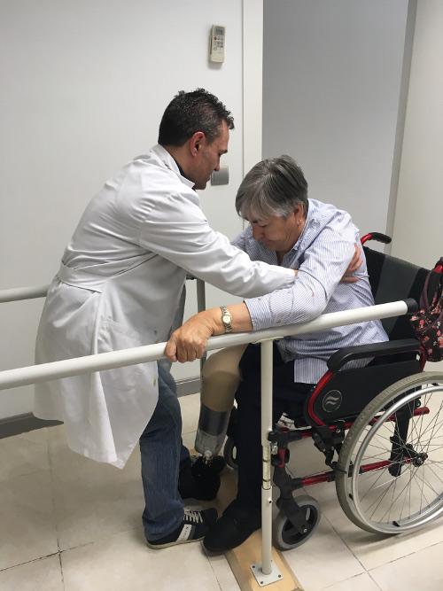 Profesional ayudando a paciente en silla de ruedas