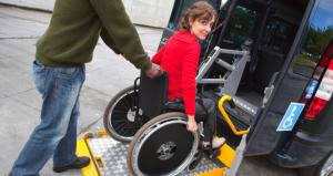 Mujer con discapacidad subiendo la rampa para acceder al taxi