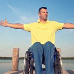 Persona en silla de ruedas disfrutando en un muelle